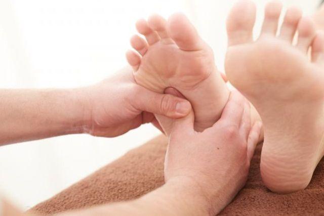 足のツボを押すセラピストの手