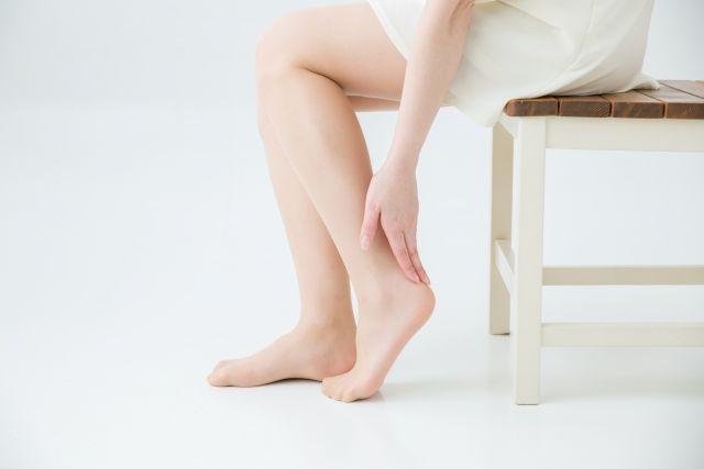 足の疲労を感じて足をさする女性