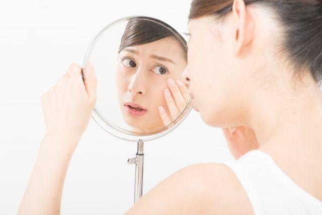 鏡を見て顔のむくみが気になる女性