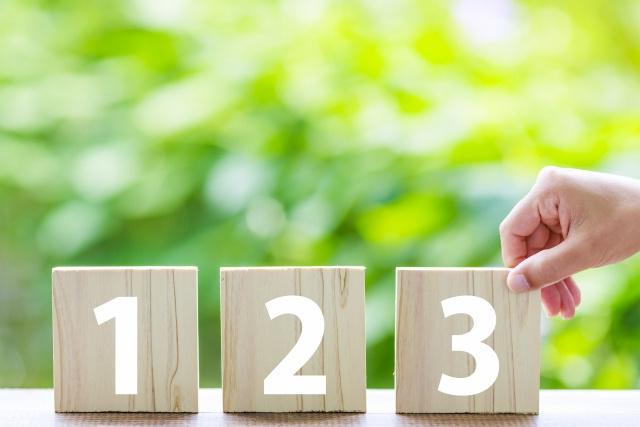 数字が書かれた積み木を掴む手