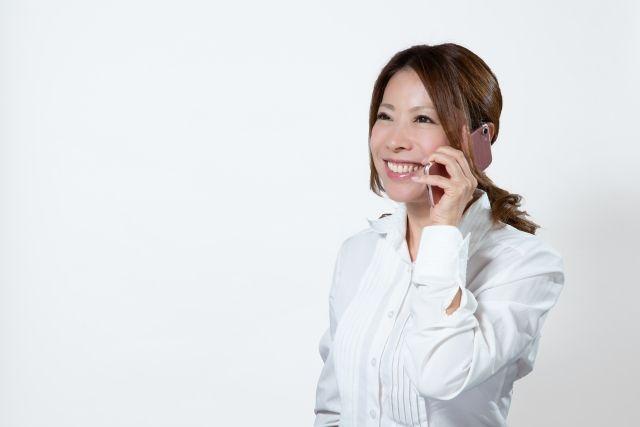 笑顔で電話をかける白いシャツを着た女性